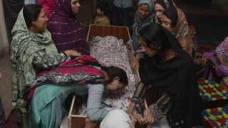 """Pakistani relatives mourn over the body of a victim during a funeral following an overnight suicide bombing in Lahore on March 28, 2016.  The toll from a suicide blast in Pakistan's Lahore rose to 69, officials said on March 28, as authorities hunted for the """"savage inhumans"""" behind the attack in a park packed with Christian families celebrating Easter Sunday. More than 200 people were injured, many of them children, when explosives packed with ball bearings ripped through crowds near a children's play area in the park in Lahore, leaving dozens dead or bloodied. / AFP / ARIF ALI"""