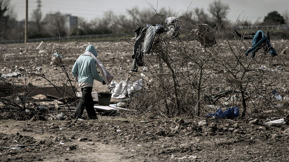 """A migrant walks past discarded clothes at the site of the former migrants camp called """"Jungle"""" in the port town of Calais, northern France, after it was dismantled by the French authorities on March 30, 2016. More than one million migrants -- about half of them Syrians -- reached Europe via the Mediterranean last year, a rate of arrival that has continued through the first three months of 2016. / AFP / PHILIPPE HUGUEN"""
