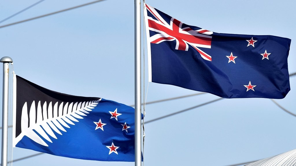 The current New Zealand flag (R) flutters next to the alternative flag (L) in Wellington on March 4, 2016.  New Zealanders began voting on March 3, on whether to adopt a new flag, in a referendum Prime Minister John Key has called a once-in-a-generation chance to ditch Britain's Union Jack from the national banner.   AFP PHOTO / MARTY MELVILLE / AFP / Marty Melville