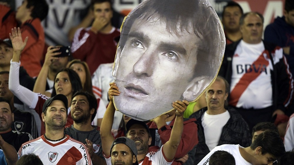 """A fan of Argentina's River Plate holds a portrait of goalkeeper Marcelo Barovero during the Copa Libertadores 2016 group 1 football match against Brazil's Sao Paulo at the """"Monumental"""" stadium in Buenos Aires, Argentina, on March 10, 2016. AFP PHOTO / JUAN MABROMATA / AFP / JUAN MABROMATA"""