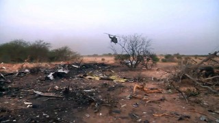 """This image grab made from a handout video filmed and released by the French Etat-Major des Armees (EMA) / Armee de Terre on July 25, 2014 shows a helicopter flying near debris at the crash site of the Air Algerie flight AH5017 in Mali's Gossi region, west of Gao. All people on board the Air Algerie passenger plane that crashed in Mali on July 24 died in the tragedy, including several families that were wiped out, France announced on July 25. There were 116 or 118 people on board, according to conflicting tolls given by the carrier and French authorities, the occupants included 54 French citizens, some of them dual nationals, as well as people from Burkina Faso, Lebanon, Algeria, Spain, Canada, Germany and Luxembourg. = RESTRICTED TO EDITORIAL USE - MANDATORY CREDIT """"AFP PHOTO / ECPAD / EMA / ARMEE DE TERRE"""" - NO MARKETING NO ADVERTISING CAMPAIGNS - DISTRIBUTED AS A SERVICE TO CLIENTS - TO BE USED WITHIN 30 DAYS FROM 07/25/2014 = / AFP / ECPAD / EMA / ARMEE DE TERRE / -"""