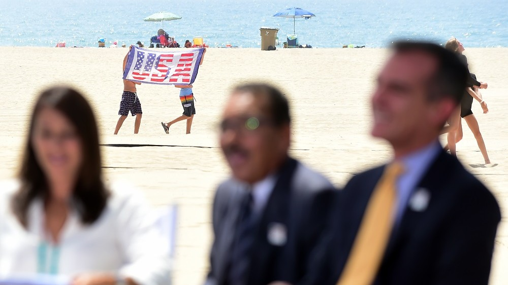 Two boys walk across the beach holding a USA flag, as Los Angeles Mayor Eric Garcetti (R) and former US Olympic Swimmer Janet Evans (L) listen as sportscaster Al Michaels addressed the audience at the Annenberg Beach House in Santa Monica, California on September 1, 2015, after the Los Angeles City Council voted unanimously to go forward with a bid to host the 2024 Summer Olympic Games, prompting the U.S. Olympic Committee to formally name Los Angeles as its official bidder for the athletic spectacle. Among those who addressed the audience besides Garcetti were sportscaster Al Michaels and former US Olympic Swimmer Janet Evans. AFP PHOTO /FREDERIC J.BROWN / AFP / FREDERIC J. BROWN