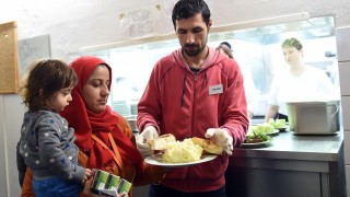 A refugee works at the food serving counter in an emergency accommodation inBerlin,Germany, 29 March 2016. Photo:BRITTAPEDERSEN/dpa