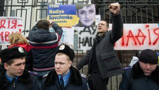 KIEV, UKRAINE - MARCH 9: A Ukrainian activist shout slogans as he puts a portrait of Nadiya Savchenko on the wall of the Russian Embassy, during a rally in support of Ukrainian pilot Nadiya Savchenko, imprisoned in Russia, near Russian Embassy, in Kiev, Ukraine, March 9, 2016. Alexey Furman / Anadolu Agency