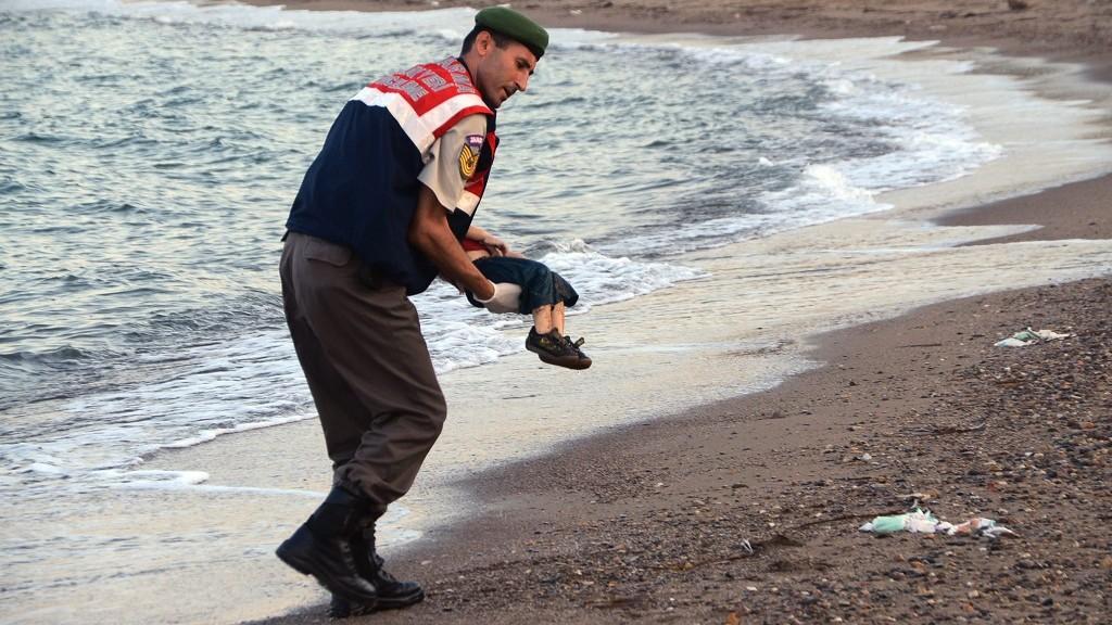 Bodrum, 2015. szeptember 3. Egy török rendõr viszi karjában Ajlan Kurdi, egy hároméves, szíriai migráns kisgyermek holttestét az Égei-tenger partján a törökországi Bodrum közelében 2015. szeptember 2-án. A fiút és családját szállító csónak elsüllyedt Törökország és a görög Kosz-sziget között. A gyermek anyja és testvére életét veszítette.  (MTI/EPA/Dogan News Agency)