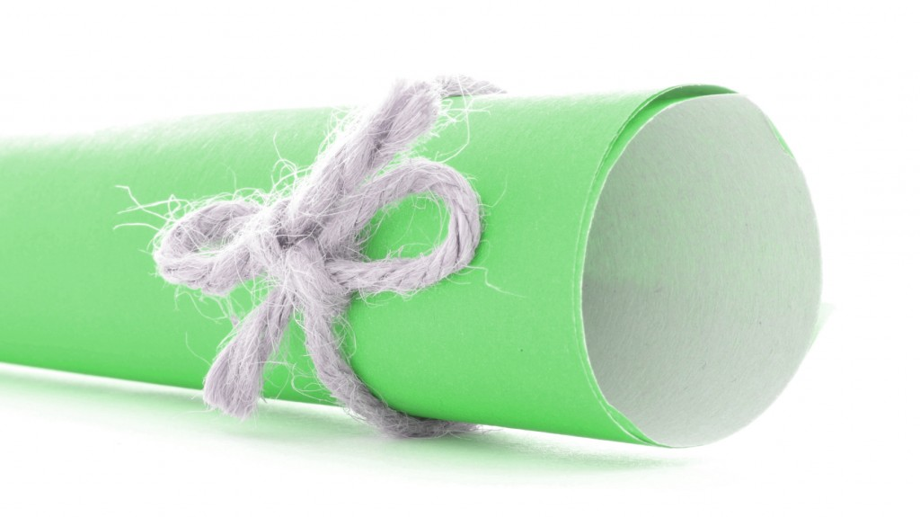 Handmade natural cord bow tied on green letter tube isolated