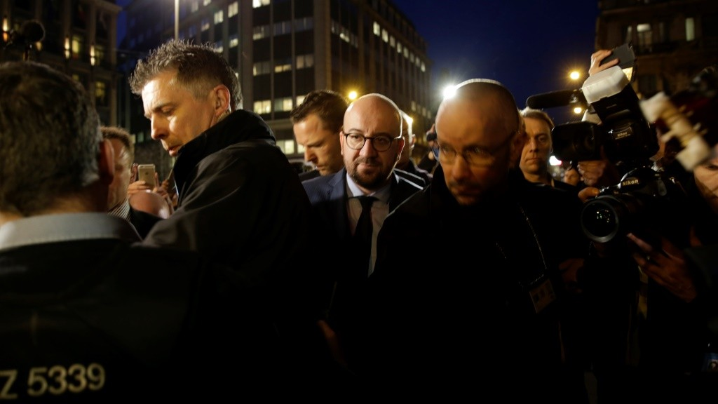 Belgian Prime Minister Charles Michel (C) is surrounded by security and journalists as he arrives at a makeshift memorial in front of the stock exchange at the Place de la Bourse (Beursplein) in Brussels on March 22, 2016, following triple bomb attacks in the Belgian capital that killed about 35 people and left more than 200 people wounded. A series of explosions claimed by the Islamic State group ripped through Brussels airport and a metro train on March 22, killing around 35 people in the latest attacks to bring bloody carnage to the heart of Europe.  AFP PHOTO / KENZO TRIBOUILLARD / AFP / KENZO TRIBOUILLARD