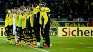 Dormund's players line up to show their respects after the death of a fan during the German first division Bundesliga football match Borussia Dortmund v 1 FSV Mainz 05 in Dortmund, on March 13, 2016. / AFP / Sascha SCHUERMANN / RESTRICTIONS: DURING MATCH TIME: DFL RULES TO LIMIT THE ONLINE USAGE TO 15 PICTURES PER MATCH AND FORBID IMAGE SEQUENCES TO SIMULATE VIDEO. == RESTRICTED TO EDITORIAL USE == FOR FURTHER QUERIES PLEASE CONTACT DFL DIRECTLY AT + 49 69 650050