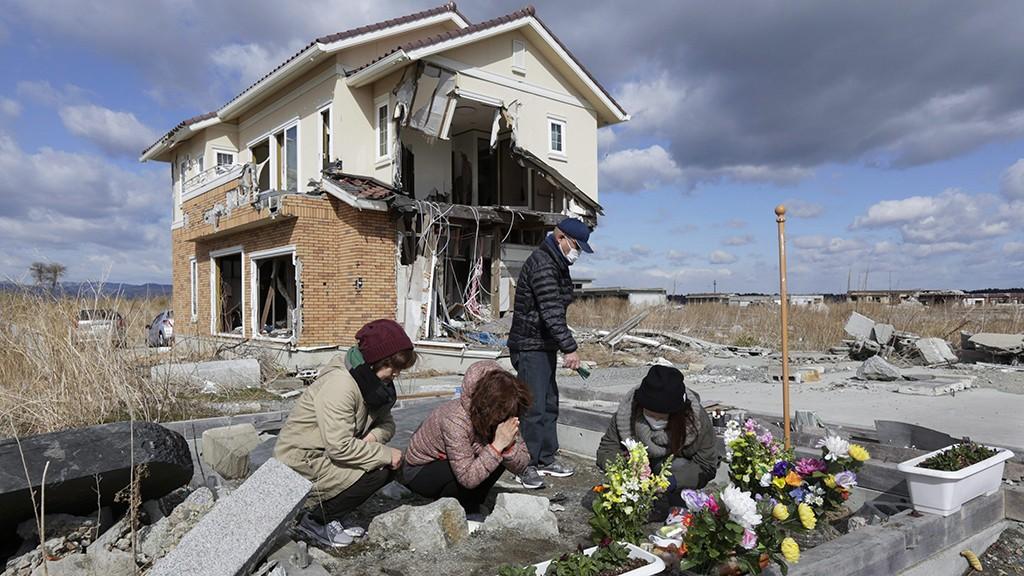 Namie, 2014. március 11.Hirata Csijoko (b2) nővérével, Macuda Hiszakóval (b) imádkozik szüleiért romos házuk előtt a Fukusima prefektúrabeli Namiében 2014. március 11-én, a Japán északkeleti partvidékén történt földrengés és szökőárharmadik évfordulóján. A Richter-skála szerinti 9-es erősségű földrengés és az általa kiváltott szökőár következtében csaknem 19 ezer ember életét vesztette vagy eltűnt. (MTI/EPA/Majama Kimimasza)