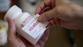 """Orosháza, 2013. június 25.""""Külsőleg"""" feliratú címkét ragaszt egy hintőporos dobozra egy szakasszisztens az orosházi Fehér Kígyó Gyógyszertárban 2013. június 25-én. Egy rendeletmódosítás szerint a gyógyszertárak szaklétszámát 2013 szeptemberétől a gyógyszertár nyitvatartási ideje, valamint a patikában befogadott vények száma határozná meg.MTI Fotó: Rosta Tibor"""