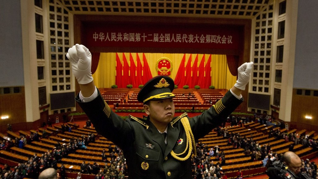 Peking, 2016. március 16. Egy katonazenekar karmestere vezényel, mialatt a az Országos Népi Gyûlés (NPC), vagyis a kínai parlament képviselõi elhagyják a pekingi Nagy Népi Csarnok kongresszusi termét 2016. március 16-án, a parlament éves ülésszakának zárónapján. (MTI/AP/Ng Han Guan)