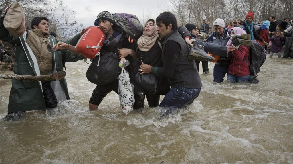 Idomeni, 2016. március 14. A macedón határ mellett fekvõ Idomeni görög falu közelében lévõ táborukból útnak indult migránsok a határon emelt macedón védõkerítést megkerülve, egy folyón kelnek át, hogy bejussanak Macedóniába 2016. március 14-én. (MTI/AP/Vadim Ghirda)