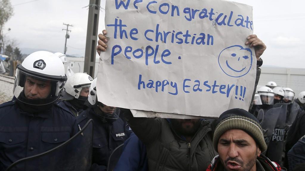 """Idomeni, 2016. március 27. """"Gratulálunk a keresztény embereknek. Boldog húsvétot!!!"""" feliratú plakátot emel a magasba egy férfi a görög rohamrendőrök sorfala előtt a macedón határ mellett fekvő Idomeni görög falu közelében lévő migránstáborban, amelynek lakói a határ megnyitását követelik 2016. március 27-én. Ezrek rekedtek a határ görög oldalán, mert Macedónia, Szerbia, Horvátország és Szlovénia lezárta határait a bevándorlók előtt. (MTI/AP/Darko Vojinovic)"""