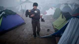 A father carries his child as he wades through mud after heavy rainfall in the refugee camp at the Greek-Macedonian border near Idomeni, Greece, 08 March 2016. Only a few refugees fromSyria and Iraq are allowed to cross into Macedonia each day. Photo:KAYNIETFELD/dpa