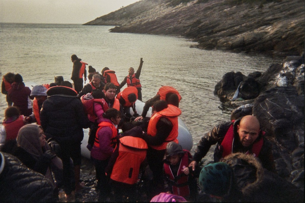 Refugees help each other to get off the dinghy. There have been no volunteers to help.