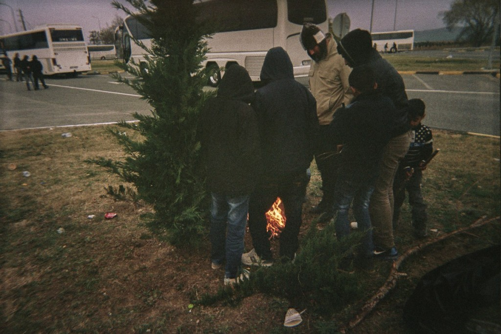 Refugees stand around a fire. Because the wood was wet, they burned trash and their last clothes to keep themselves warm. They had to stay outside the buses.