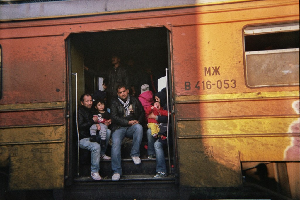 Refugees looking out a overcrowded train in Macedonia. On the rigtht a mother holds her crying kid in her arms. The doors were not able to close and have been open during the drive.