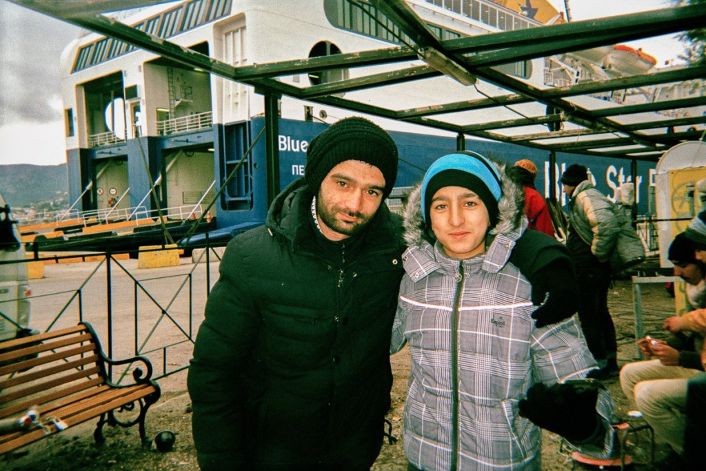 Amer and his brother Hashem stay  in front of the ferry in Mytilini Port, Lesbos. This ferry brings tourists and refugees from greek islands to Athens.