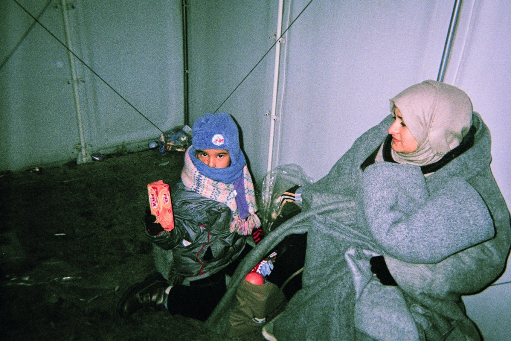 Son Kerim and Dyabs' wife in a transfer-camp are covered in blankets in a transfer camp in Macedonia.