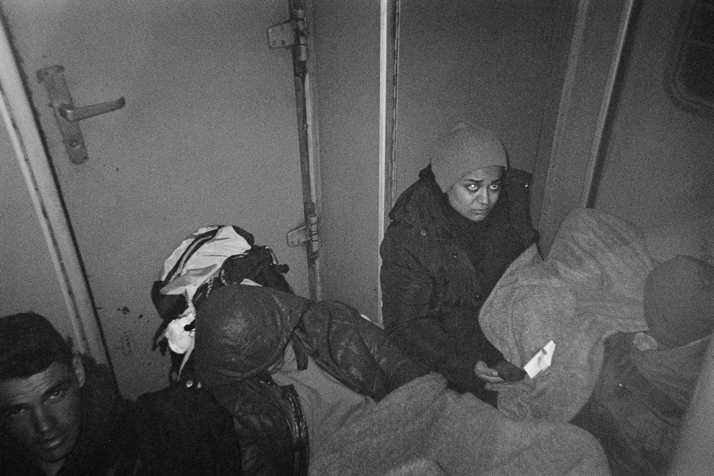 Refugees sit in front of a toilet in an overcrowded train from Macedonia to Serbia. A ticket cost 25 euros