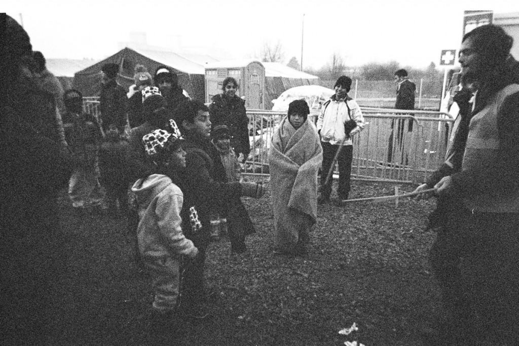 A volunteer entertains the younger refugees outside a camp between Croatia and Slovenia. The kids try to imitate his tricks.
