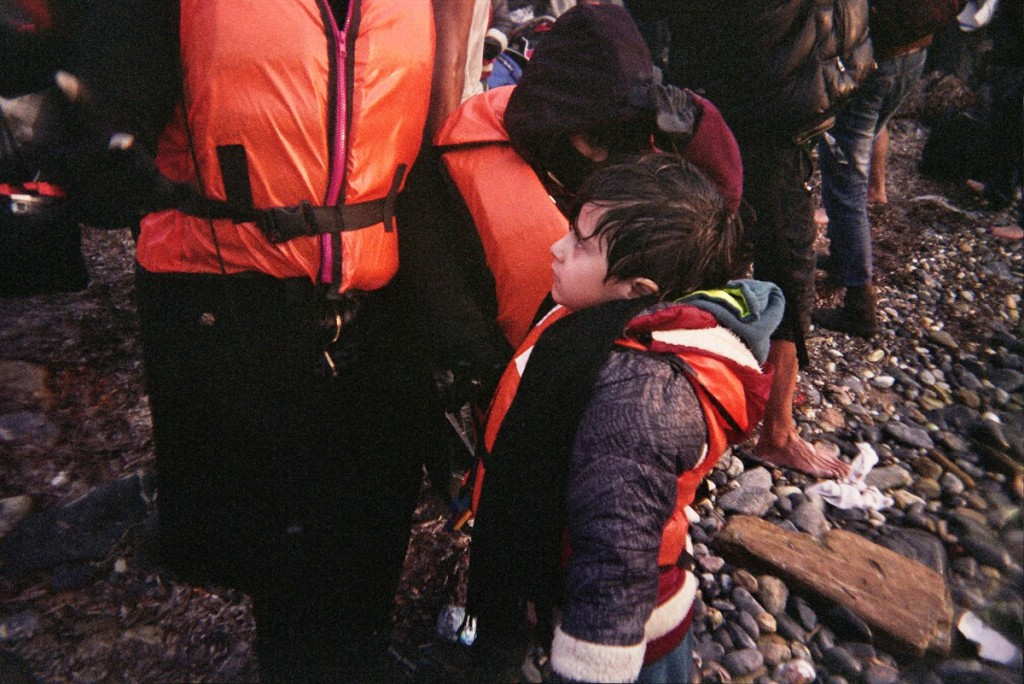 A young boy stands with his wet clothes on the stony beach right after they stranded.