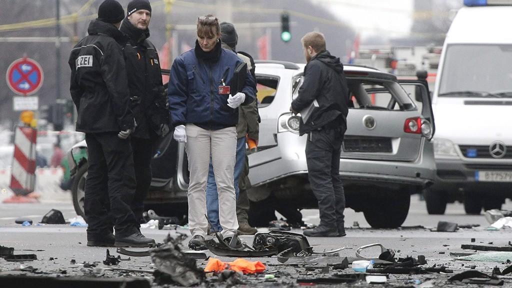 Berlin, 2016. március 15.Helyszínelők dolgoznak egy felrobbantott személygépkocsinál 2016. március 15-én Berlinben. Az autó a német főváros Charlottenburg nevű városrészében egy forgalmas úton haladt, amikor működésbe lépett a robbanószerkezet. A sofőr életét veszítette, sérültje nincs a robbantásnak. Egy sajtóértesülés szerint a robbantásos merénylet nem terrortámadás volt, hanem valószínűleg szervezett bűnözői csoportok közötti leszámolás állhat a háttérben. (MTI/AP/Michael Sohn)