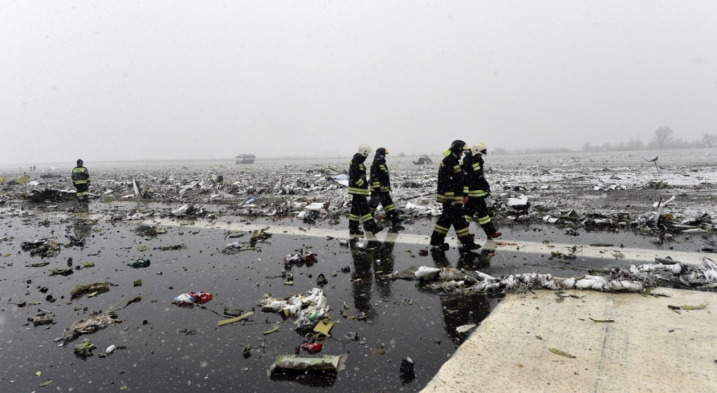 Russian emergency rescuers work on the wreckage of the flydubai passenger jet which crashed, killing all 62 people on board as it tried to land in bad weather in the city of Rostov-on-Don on March 19, 2016.  The plane, which came from Dubai, was making its second attempt to land when it missed the runway, erupting in a huge fireball as it crashed, leaving debris scattered across a wide area. The ministry said more than 700 rescuers and 100 vehicles were combing the area in driving wind and snow where the wreckage was strewn, with investigators confirming one of the plane's black boxes had been retrieved.  / AFP / -