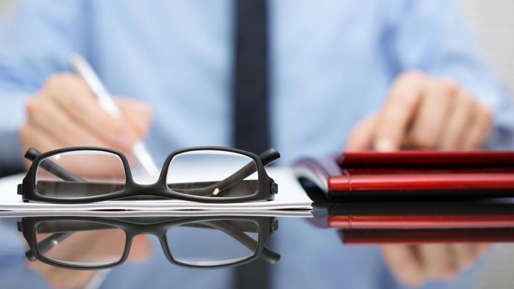 blurred businessman is working in office , focus is on eyeglasses