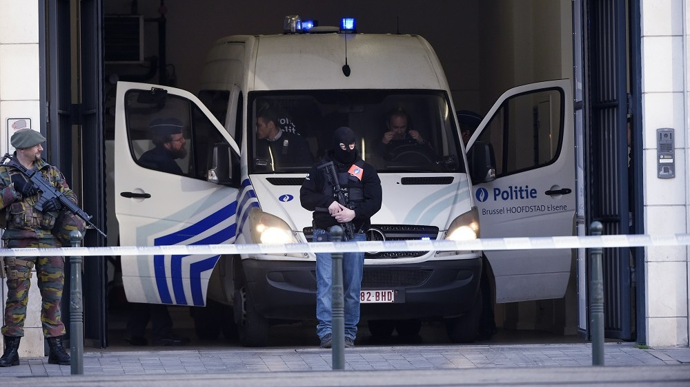 """Police officers stand in front of a vehicle at Brussels courthouse on April 13, 2016, before the hearing of top Paris attacks suspect Mohamed Abrini. Paris attacks suspect Mohamed Abrini confessed on April 10 to being """"the man in the hat"""" caught on video with suicide bombers at Brussels airport last month, images that had sparked a massive manhunt. / AFP PHOTO / JOHN THYS"""