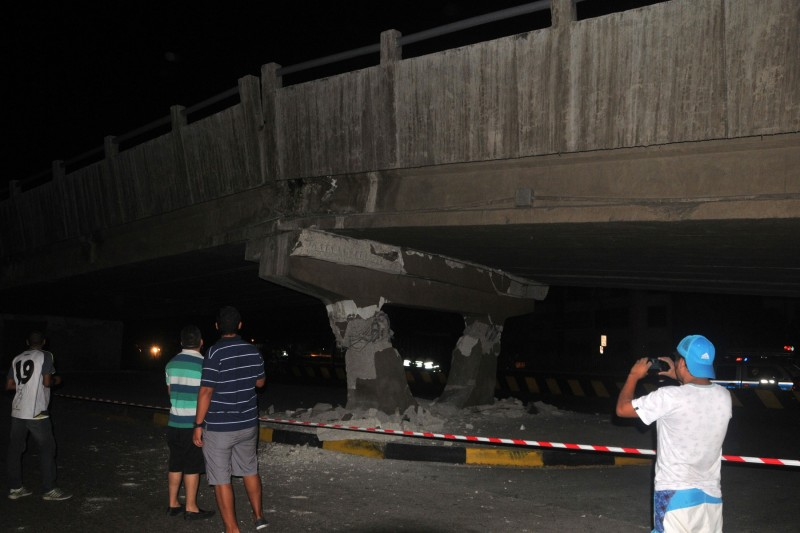 People take pictures of a collapsed bridge in Guayaquil, Ecuador, after a powerful earthquake hit the country on April 16, 2016.  At least 28 people were killed when a powerful 7.8-magnitude earthquake struck Ecuador on Saturday, knocking down buildings in the country's largest city Guayaquil and cutting power in the capital Quito. The quake also rattled northern Peru and southern Colombia, according to authorities in those countries, although no casualties were reported. / AFP PHOTO / JOSE SANCHEZ LINDAO