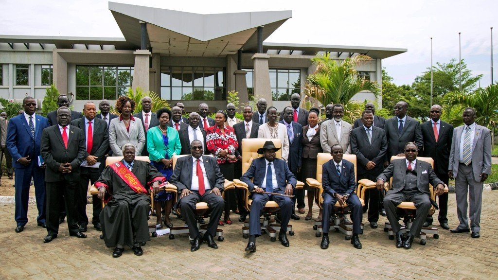 (Seated from 2nd L) First Vice President of South Sudan and former rebel leader Riek Machar, South Sudan President Salva Kiir and Second Vice President of South Sudan James Wani Igga pose along with the 30 members of the new cabinet of the Transitional Government outside the Cabinet Affairs Ministry in Juba on April 29, 2016. South Sudan President Salva Kiir has named his transitional unity government, sharing power with ex-rebels in a key step in a long-delayed peace process, a decree read out on April 29 said. Under terms of an August 2015 peace deal, the 30 ministerial posts are split between Kiir, former rebel chief turned first vice president Riek Machar, opposition and other parties.  / AFP PHOTO / ALBERT GONZALEZ FARRAN