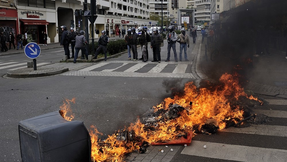 FRANCE, Rennes : A trash can burns in the street as protesters clash with anti-riot police during a rally against the French government's labour law reforms in Rennes, western France, on April 28, 2016.Protesters clashed with police in Paris and western France on April 28 as workers and students across the country made a new push for the withdrawal of a hotly contested labour bill. Demonstrations as well as work stoppages, notably in the aviation and public transport sectors, are planned across France in the latest actions in a protest wave that began two months ago - Pierre Roth
