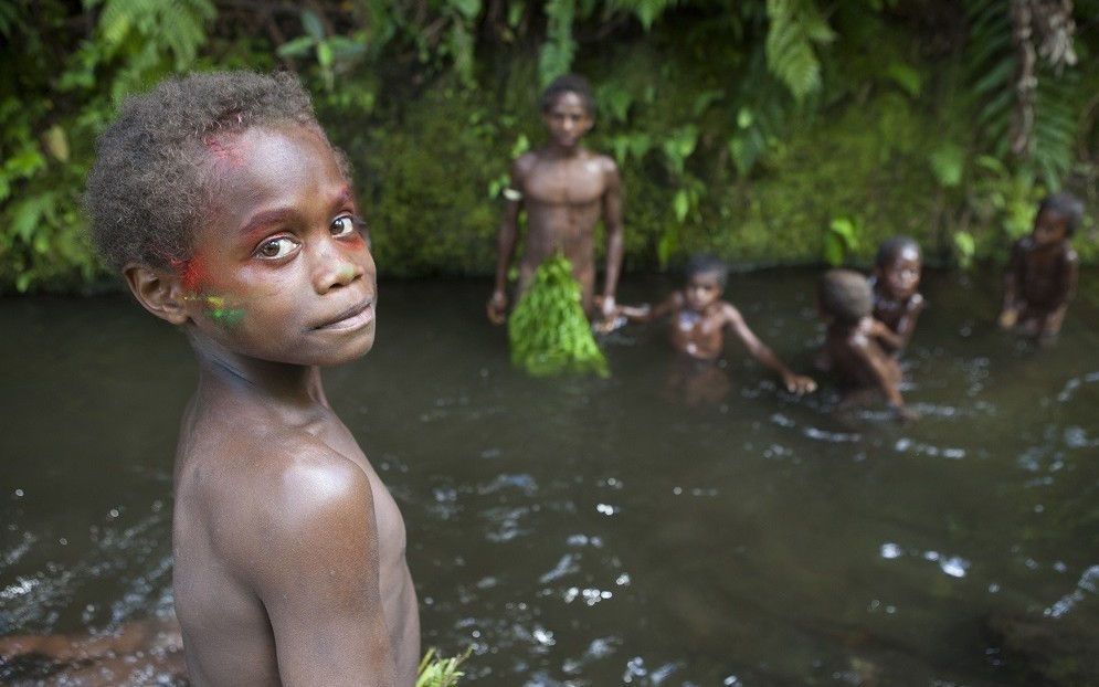 TANNA ISLAND  Portrait of Boy in a river bank - Tanna Vanuat.  Mangao, 8 years old, the future chieftain of his village of Yakel  Biosphoto / Antoine Boureau