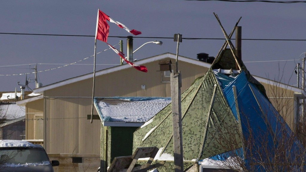 In this December 17, 2011 photo, a tattered Canadian flag flies over a teepee in Attawapiskat, Ont. Two government audits show Ottawa is earmarking about a billion dollars a year to build and repair First Nations infrastructure, but its myriad officials are not keeping proper tabs on how the money is spent. THE CANADIAN PRESS/Frank Gunn