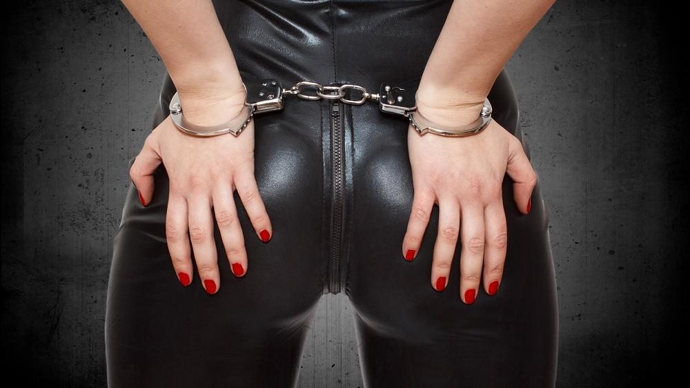 Sexy dominatrix, hands on ass in handcuffs, closeup