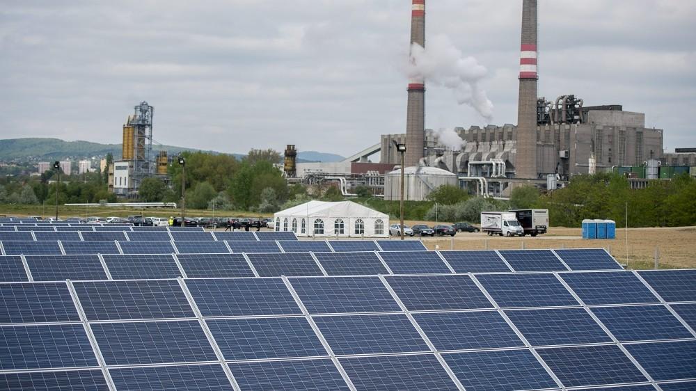 Pécs, 2016. április 28. Napelem panelek az új pécsi fotovoltaikus erõmûben az átadás napján, 2016. április 28-án. A több mint négymilliárd forintos uniós és állami támogatás segítségével megvalósult beruházásnak köszönhetõen éves szinten akár 15 ezer tonnával is csökkenhet az ország szén-dioxid-kibocsátása. A háttérben a pécsi hõerõmû látható. MTI Fotó: Sóki Tamás