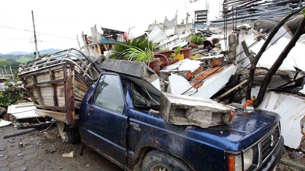 Pedernales, 2016. április 17. Megrongálódott személygépkocsi egy összeomlott lakóház mellett az ecuadori Pedernalesben 2016. április 17-én, egy nappal az után, hogy a Richter-skála szerint 7,8-as fokozatú földrengés rázta meg a latin-amerikai ország északnyugati partvidékét. A természeti katasztrófa halálos áldozatainak száma 233-ra emelkedett, több százan megsérültek. (MTI/EPA/Jose Jacome)