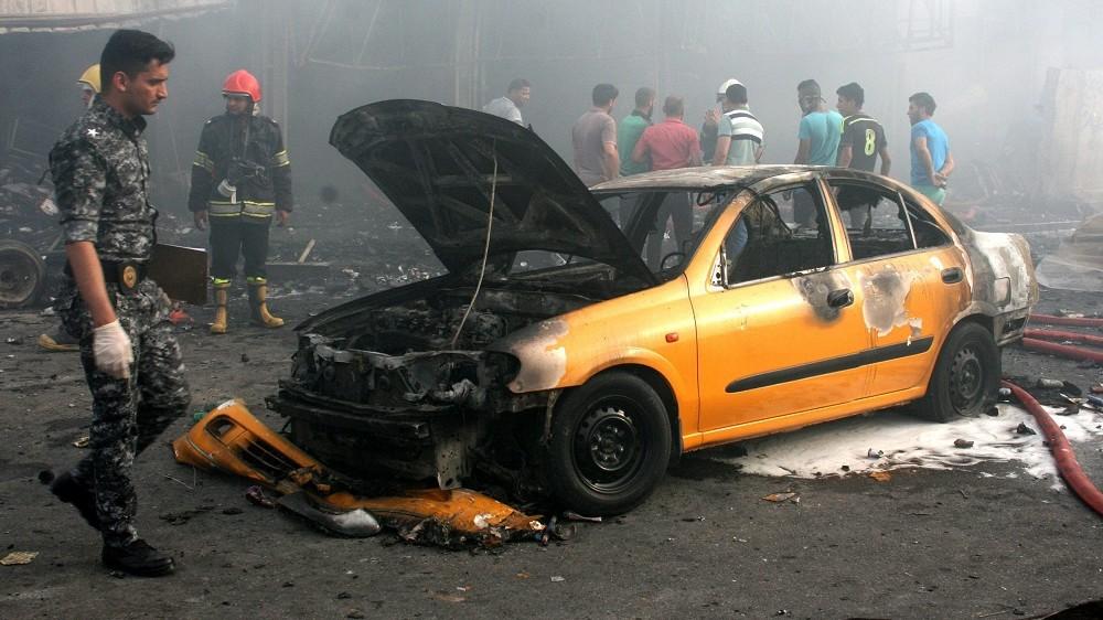 Bagdad, 2016. április 25. Iraki rendõr és tûzoltók helyszínelnek egy kiégett gépkocsi roncsánál, miután pokolgép robbant Bagdad egyik, többségében síiták által lakott keleti kerületében 2016. április 25-én. A legkevesebb tizenegy halálos áldozatot követelõ detonáció elkövetését egyetlen szervezet sem vállalta magára. (MTI/EPA/Ahmed Ali)