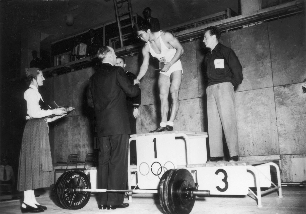 27th July 1952:  Tamio 'Tommy' Kono (1930 -  ) of the USA, being presented with his medal  on the winner's rostum at the Helsinki Olympics,  after coming first in the Lightweight Weightlifting class event. To his left E Lopatin of the USSR (silver) and V Barberis of Australia (bronze), on his right.  (Photo by Keystone/Getty Images)