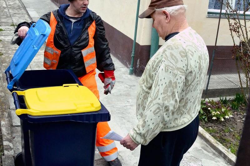 Budapest, 2013. március 25.Szücs Zoltán, a Fővárosi Közterület-fenntartó (FKF) Zrt. dolgozója szelektív hulladékgyűjtéshez alkalmas kukákat ad át Budapest X. kerületében, a Bodza utcában 2013. március 25-én. Az FKF munkatársai a fővárosban megkezdték a sárga és kék fedelű, 120 és 240 literes gyűjtőtartályok kiszállítását a házakhoz, amivel a szelektív hulladékgyűjtést oldják meg.MTI Fotó: Balaton József