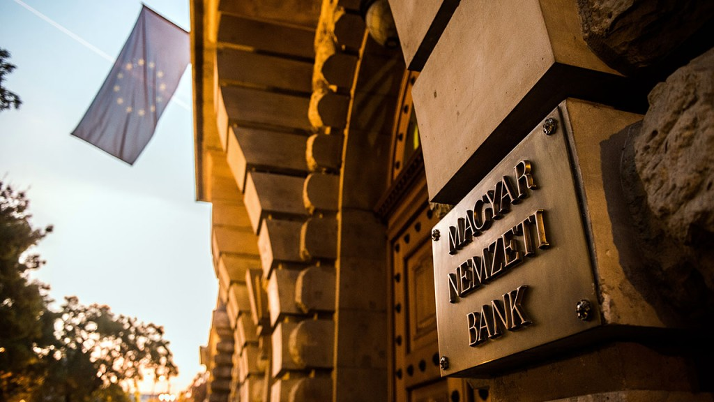 A sign sits on display at the entrance to the Hungarian central bank, also known as Magyar Nemzeti Bank, as a flag of the European union flies in the distance, in Budapest, Hungary on Tuesday, Nov. 3, 2015. Hungary's central bank has extended its Funding for Growth Plan into 2016, seeking to boost banks' lending via new facilities, according to a National Bank of Hungary statement. Photographer: Akos Stiller/Bloomberg via Getty Images