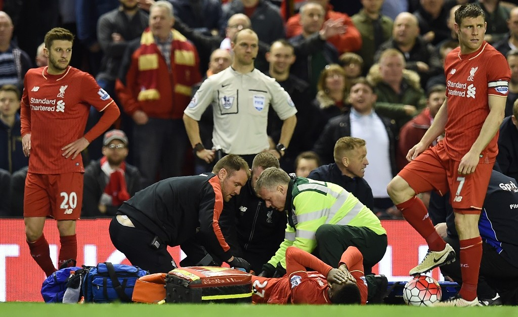 Liverpool's Belgian striker Divock Origi (C) receives medical assistance after being injured during the English Premier League football match between Liverpool and Everton at Anfield in Liverpool, north west England on April 20, 2016. / AFP PHOTO / PAUL ELLIS / RESTRICTED TO EDITORIAL USE. No use with unauthorized audio, video, data, fixture lists, club/league logos or 'live' services. Online in-match use limited to 75 images, no video emulation. No use in betting, games or single club/league/player publications.  /