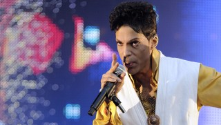 (FILES): This June 30, 2011 file photo shows US singer and musician Prince performing on stage at the Stade de France in Saint-Denis, outside Paris.  Pop icon Prince was treated in hospital on April 15, 2016 after a bout of flu worsened in mid-air, forcing his private jet to make an unscheduled landing, his publicist told AFP. / AFP PHOTO / BERTRAND GUAY