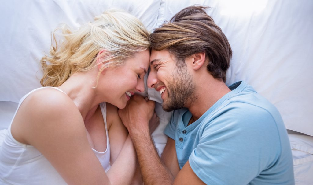 Cute couple relaxing on bed smiling at each other