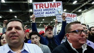 Supporters of Republican presidential candidate Donald Trump hold banners while he speaks during a rally in Bethpage Long Island, New York on April 6, 2016. Trump looks to bounce back from his unsettling presidential primary los in Wisconsin, training his sights in the next White House contests on friendlier ground -- his home state of New York. / AFP PHOTO / KENA BETANCUR