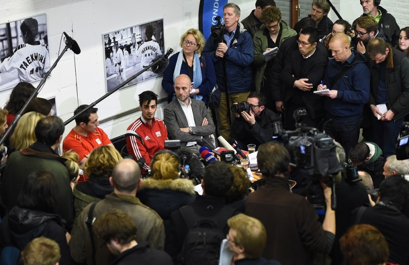 """Journalists surround Belgian Taekwondo athlete Mourad Laachraoui, younger brother of Brussels attacks suspect Najim Laachraoui, as he gives a press conference on March 24, 2016, at the headquarters of the Francophone Belgian Taekwondo Association in Ukkel/ Uccle, Brussels, two days after a triple bomb attack, claimed by the Islamic State group, hit Brussels' airport and the Maelbeek - Maalbeek metro station, killing 31 people and wounding 270 others.  Mourad Laachraoui """"firmly"""" condemned his brothers actions saying there had been no contact between the pair since his older brother left Belgium for Syria more than two years ago. / AFP PHOTO / BELGA / EMMANUEL DUNAND / Belgium OUT"""