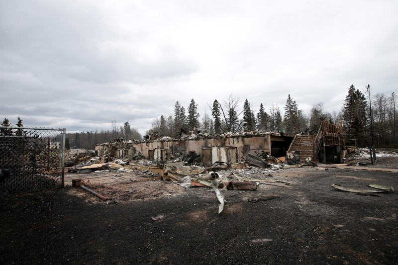 Burned out homes are pictured in the Abasand neighbourhood of Fort McMurray, Alberta, Canada, May 9, 2016 after wildfires forced the evacuation of the town. Fort McMurray is still 90-percent intact despite a week of damage from the wildfires devastating Canada's oil sands region, Alberta's premier said after touring the deserted city on Monday. Firefighters warned however that the tens of thousands of residents evacuated from the western oil city would not be able to return for at least two weeks.  / AFP PHOTO / POOL / CHRIS WATTIE
