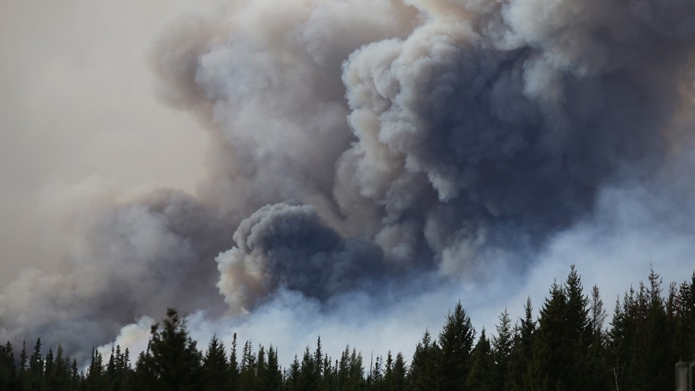 (FILES) This file photo taken on May 7, 2016 shows flames and smoke rising off Highway 63 outside Fort McMurray, Canada. Mandatory evacuation orders were issued for some 20 oil sands camps and facilities in Canada's Alberta province due to smoke and flames from the Fort McMurray wildfire, regional emergency officials said May 17, 2016. The evacuation orders, which affect some 8,000 people, were issued late Monday (0200 GMT Tuesday) for a region between Fort McMurray and a few kilometers south of the town of Fort MacKay, officials said.   / AFP PHOTO / Cole Burston/