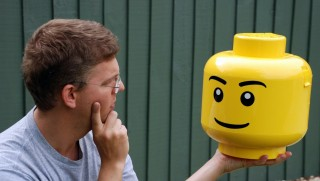 """This undated handout picture released by the University of Canterbury at Christchurch on May 23, 2016 shows associate professor Christoph Bartneck from the university holding a Lego container at the campus. Lego products are becoming increasingly violent as toymakers engage in an """"arms race"""" to retain children's attention in the digital age, New Zealand researchers said on May 23, 2016.  The University of Canterbury team said child's play was becoming more brutal, with a higher proportion of weapons appearing among Lego's building blocks and war-like scenarios featuring in its themed kit sets. / AFP PHOTO / University of Canterbury / STR / ----EDITORS NOTE ----RESTRICTED TO EDITORIAL USE MANDATORY CREDIT """" AFP PHOTO / UNIVERSITY OF CANTERBURY"""" NO MARKETING NO ADVERTISING CAMPAIGNS - DISTRIBUTED AS A SERVICE TO CLIENTS - NO ARCHIVES"""